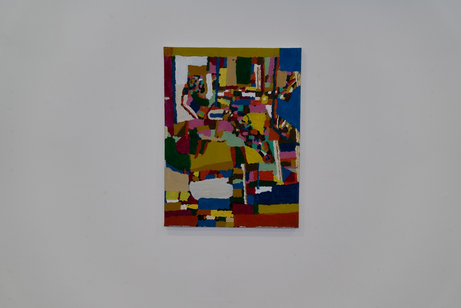 This is an image of a painting on paper centred on a white wall. The painting is made up of very colourful patches of acrylic paint that are part abstract and part form a figure seated almost in profile in an interior space.