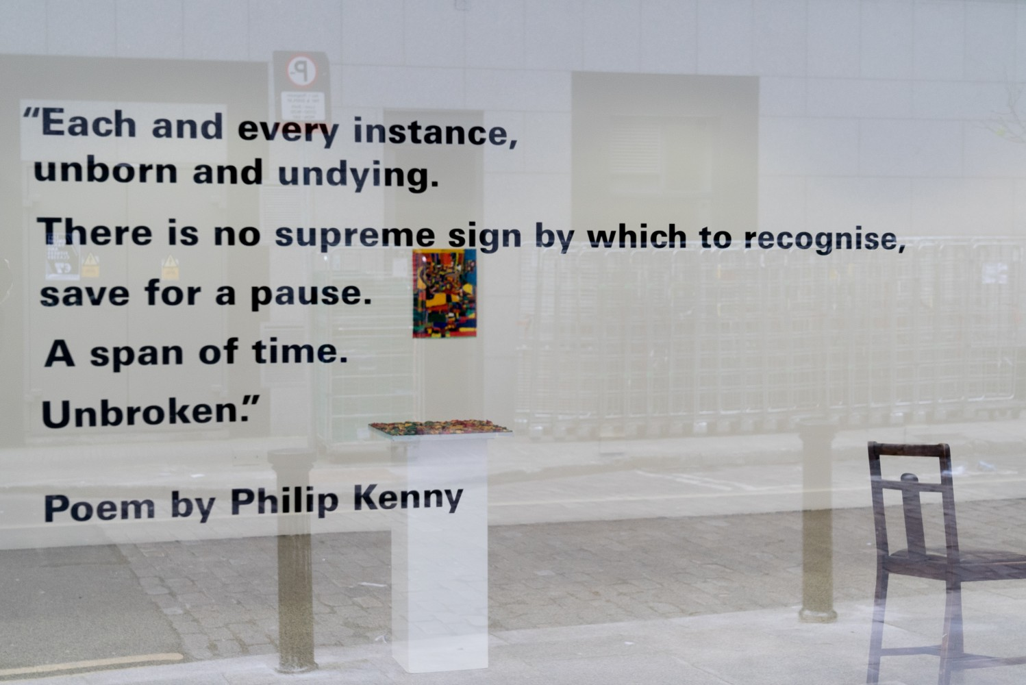 Six lines of a poem and the name of the poet in vinyl in bold black sans serif font on the glass of a gallery. In the background inside the gallery is a colourful painting on a white wall, a flat colourful artwork on a white plinth and on the right hand side part of a chair sculpture. The floor of the gallery is speckled grey. In the glass there is a reflection of the street including a path, cobbles and a parking sign.