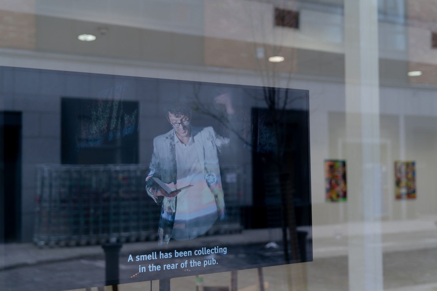 A large flat screen TV viewed through the glass window of a gallery takes up most of the frame. The TV shows a man with dark hair and glasses reading from a book, the background behind him is black. At the bottom of the screen there is a caption that reads 'A Smell has been collecting in the rear of the pub'. Behind the TV we can see the ceiling floor and wall of the gallery. The street is reflected in the glass.