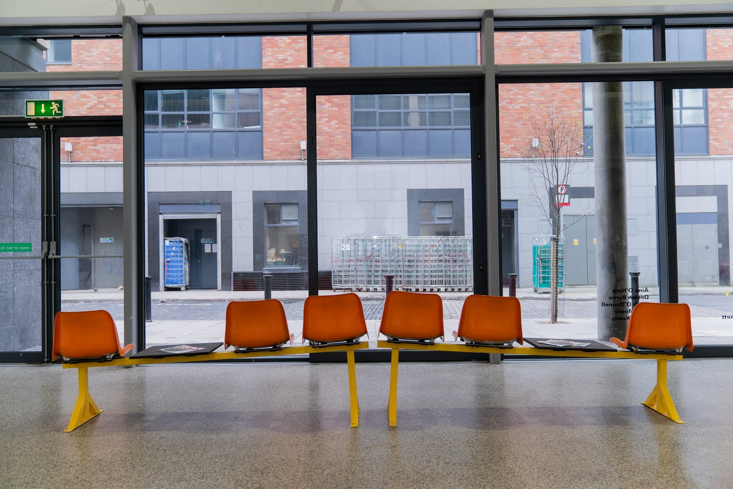 Two rows of three bright orange hospital chairs with yellow legs are seen for behind. The rows are both angled upwards so it would feel uneven if you sat on them. They are set up in front of a large window that looks out onto the street. The floor reflects the chairs slightly, it's grey with a speckled effect.