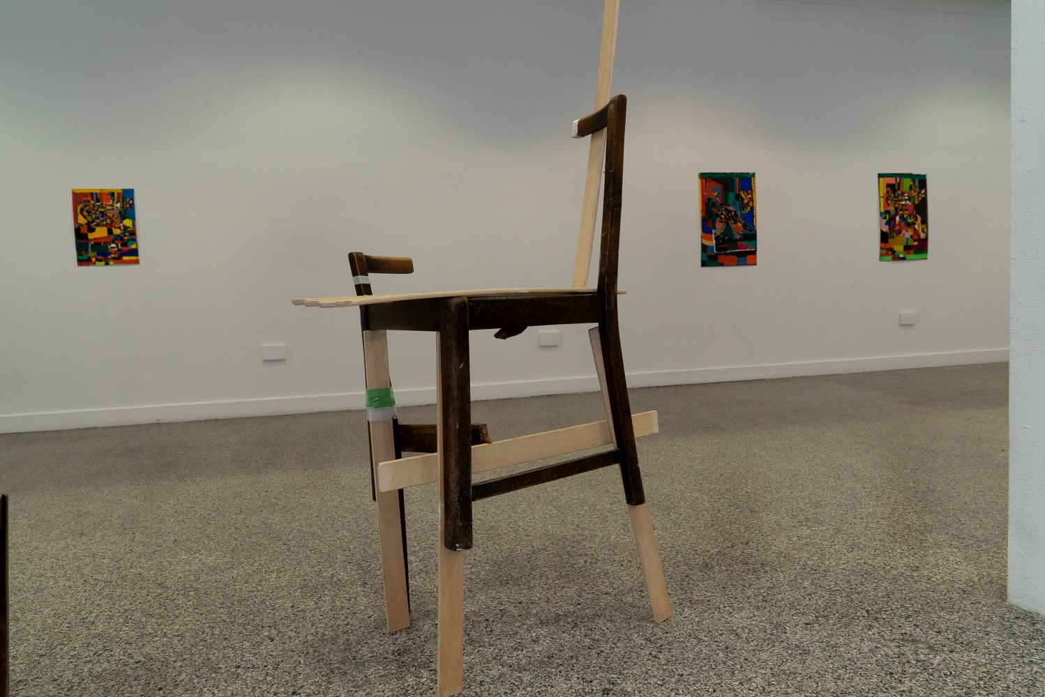 This image shows a deconstructed dark wooden chair in a gallery. The gallery wall is white and has three paintings on it. The gallery floor has a specked grey effect. On the right hand side of the image there is a column.The chair on is completely deconstructed and put back together in a strange way with lighter wood. There are three legs. One leg is taped with green tape.