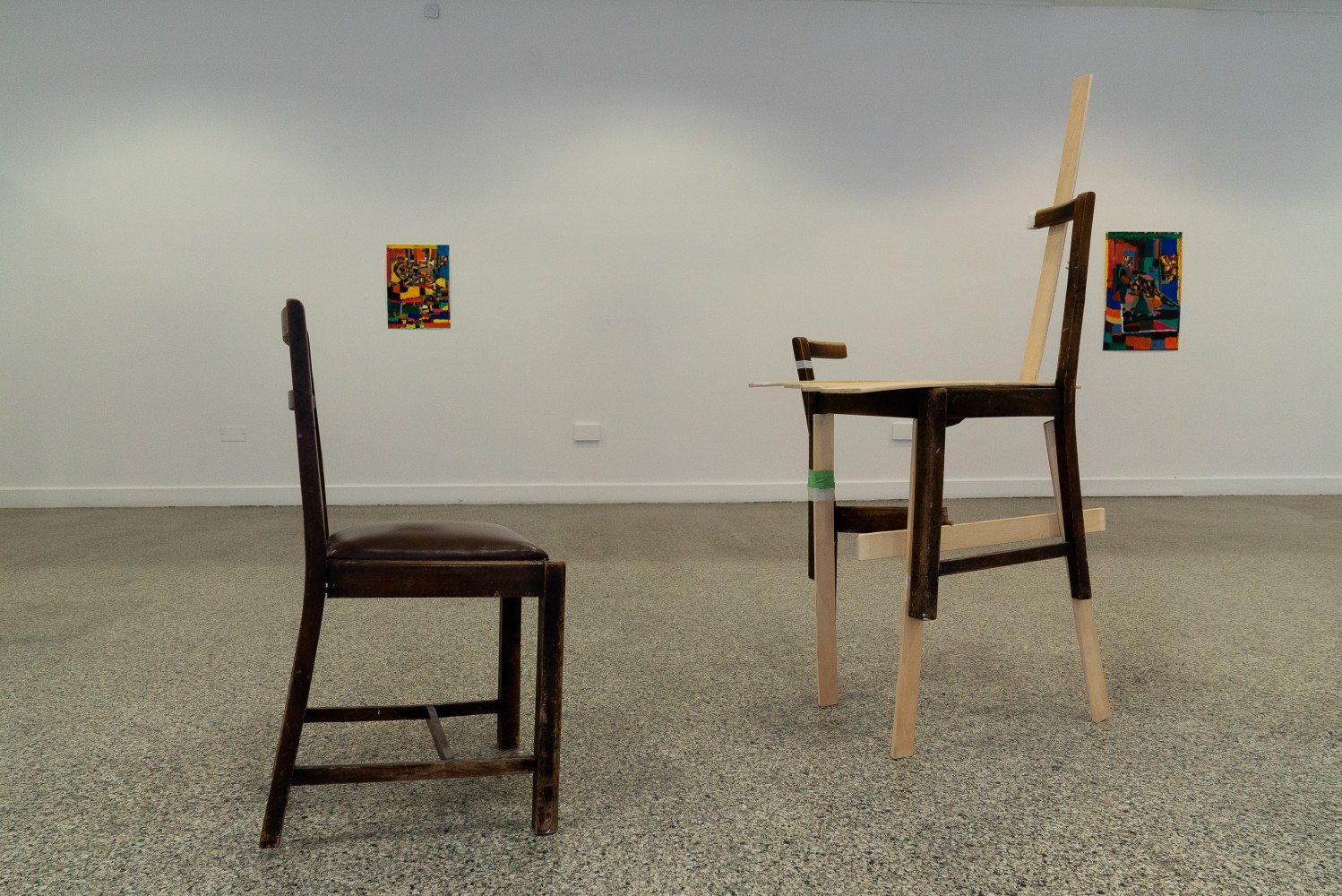 This image shows two altered or deconstructed dark wooden chairs in a gallery. There is one chair to the left of the frame another on the right. The gallery wall is white and has two paintings on it. The gallery floor has a specked grey effect. The chair on the left hand side is resting uneven on the ground, one of it's legs is slightly shorter than the others. The chair on the right hand side is completely deconstructed and put back together in a strange way with lighter wood.