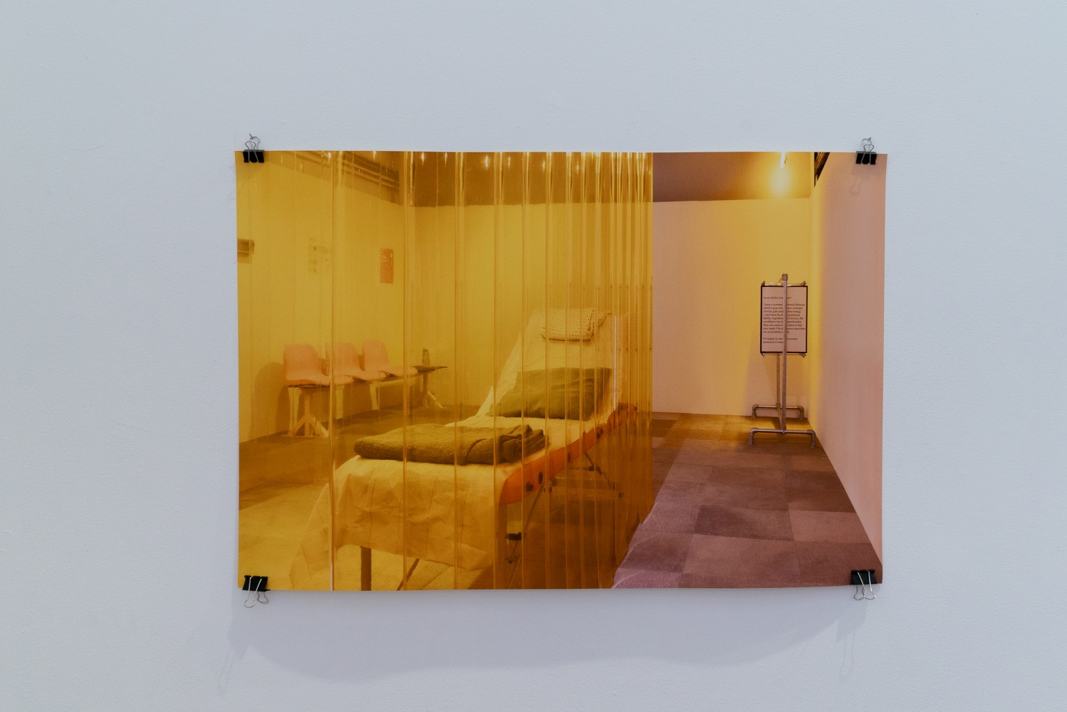 This is an image of an archival print photograph on paper on a white wall. The photograph is hung from using pins and black crocodile clips in all four corners. The photograph shows us a white walled room, with a grey carpeted floor, bathed in a yellow light. On the left hand side of the photograph there is a hospital trolly surrounded by translucent plastic yellow curtains and on our right hand side in the background of the room there is a rail with large charts hanging from it.