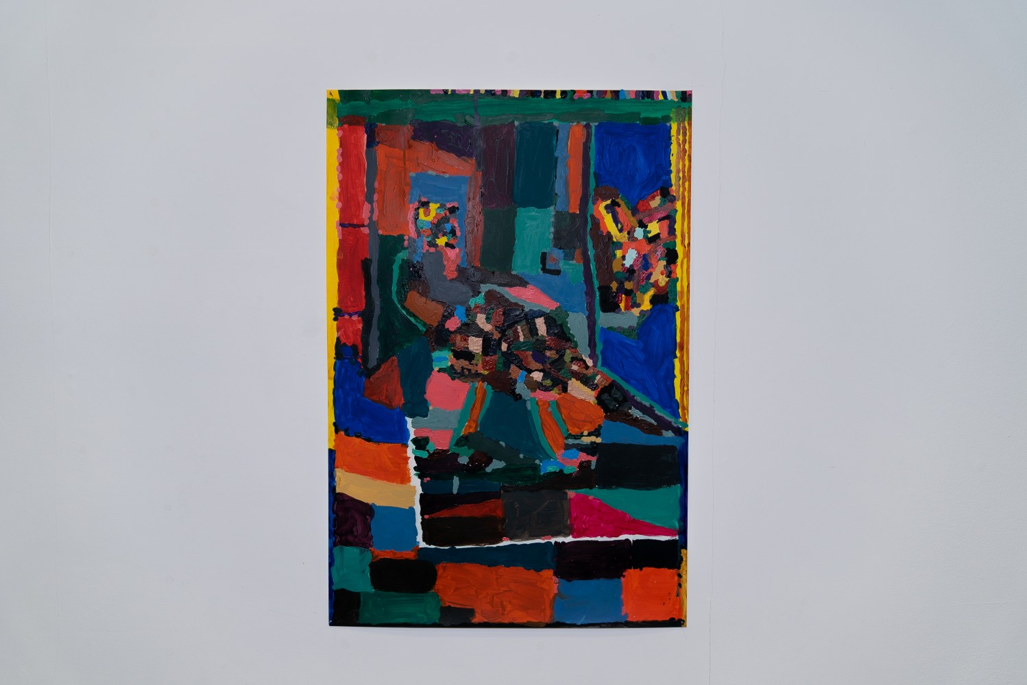This is an image of a painting on paper centred on a white wall. The painting is made up of very colourful patches of acrylic paint that are part abstract and part form a figure seated almost in profile in an interior space. The colours blue, red, black and green are prominent. The left and right hand side of the painting are edged in yellow.