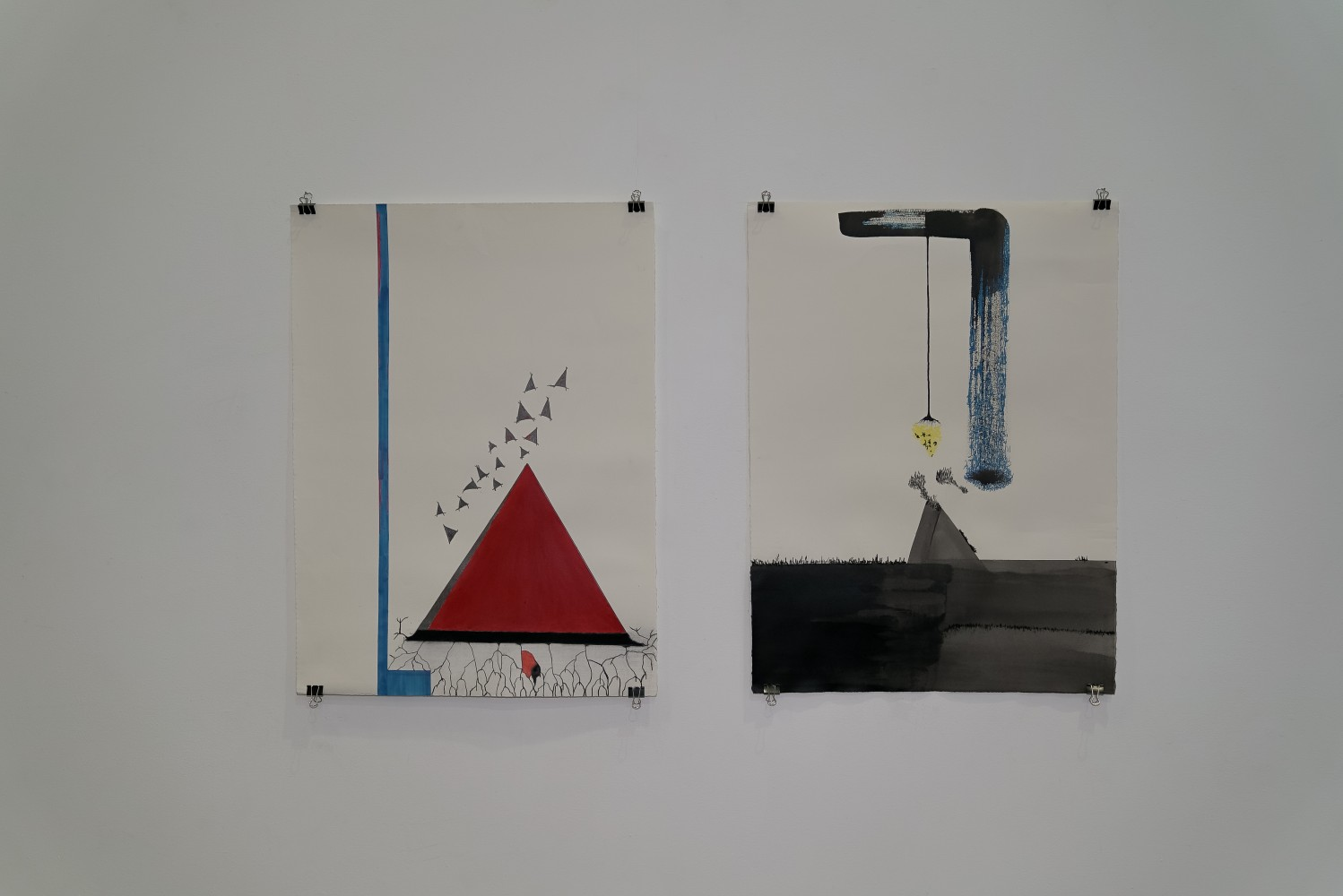 an image of two drawings on paper hung with pins and small crocodile clips from each of their four corners on a white wall. The drawings are of made of rectangles and triangles in black, red, blue and yellow of different sizes against white paper.