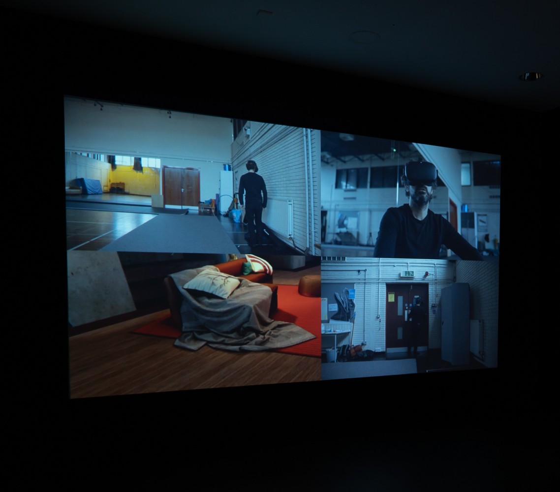 This is a still from a film that is being projected. The screen is split into four rectangles showing different angles of a gym space. Some of the angles show the artist wondering around bumping into things because he has a VR headset on. Sometimes he's moving his head and his hands around and sometimes he sits on a sofa in the gym. The gym is low lit. Sometimes it's lit with a yellow light. One of the rectangles shows what the artist is looking at in the VR headset. The VR space is a domestic living room space with seating and orange fabric bathed in a warm light.